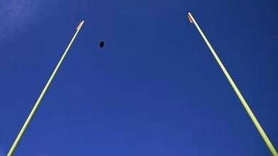 A football flies through the uprights during warmups