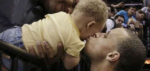 Golden State Warriors' Stephen Curry kisses his daughter,