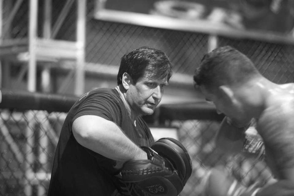 Trainer Ray Longo, left, goes over combinations with