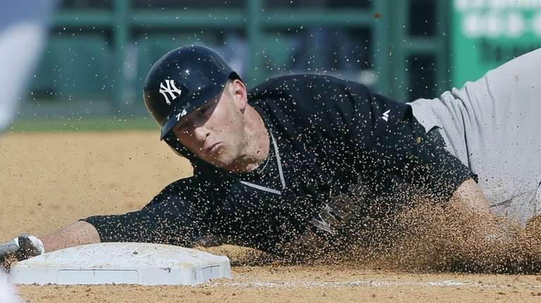 Slade Heathcott safely slides into third on a