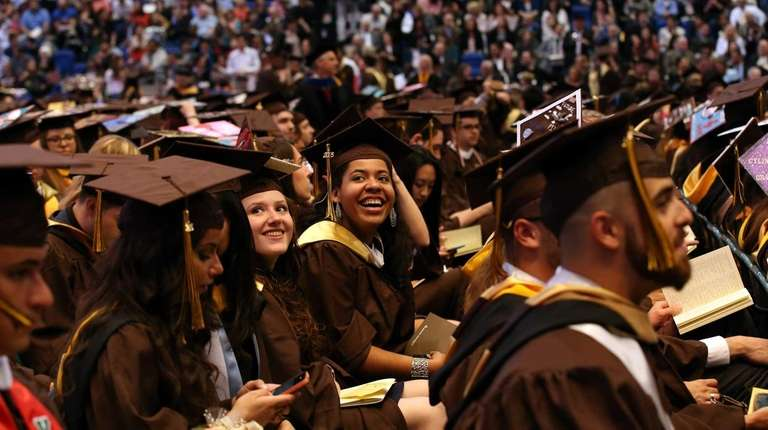 Graduates smile at their guests at Adelphi University's