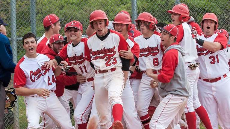 Connetquot players surround first baseman Brandon Morse (23,
