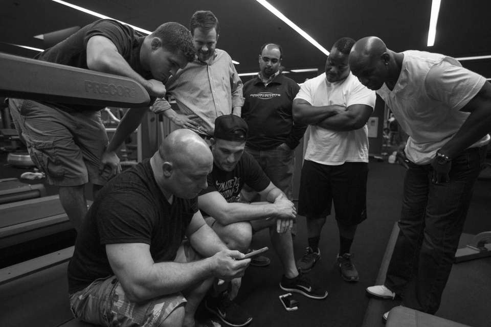 Team Weidman gathers around Matt Serra's cellphone to