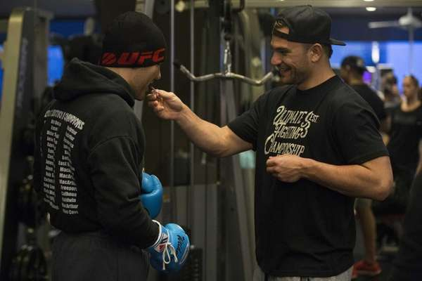 Gian Villante, right, feeds chewing gum to training