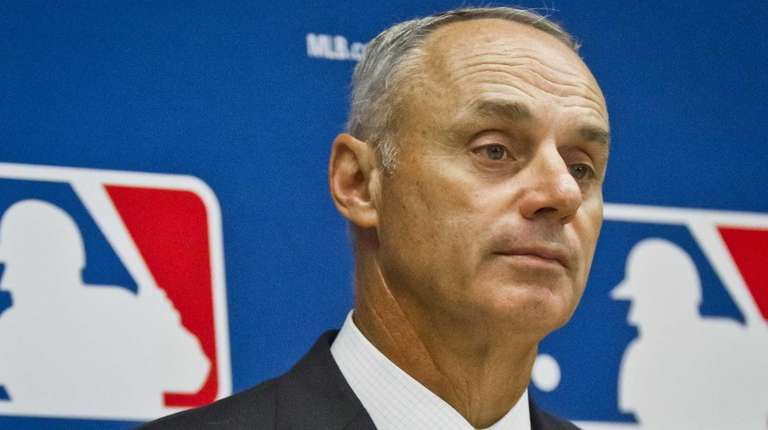 Baseball commissioner Rob Manfred listens during a press