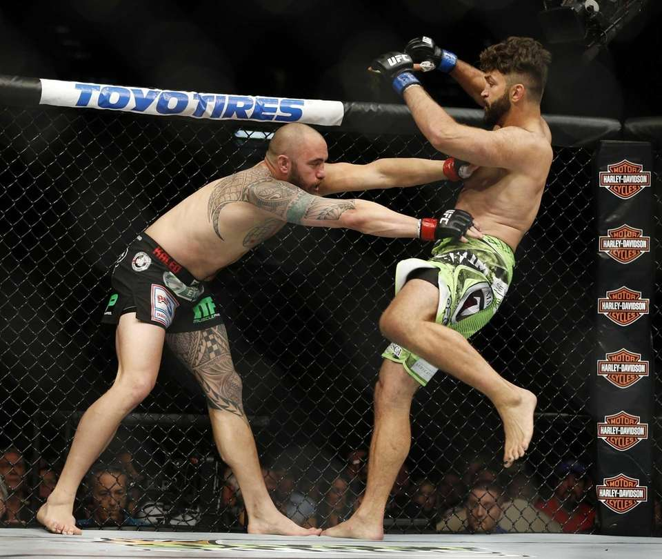 Andrei Arlovski, right and Travis Browne engage during