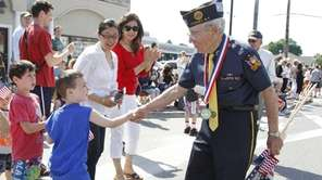 Noah Abramson, 6, shakes hands with WWII Vet