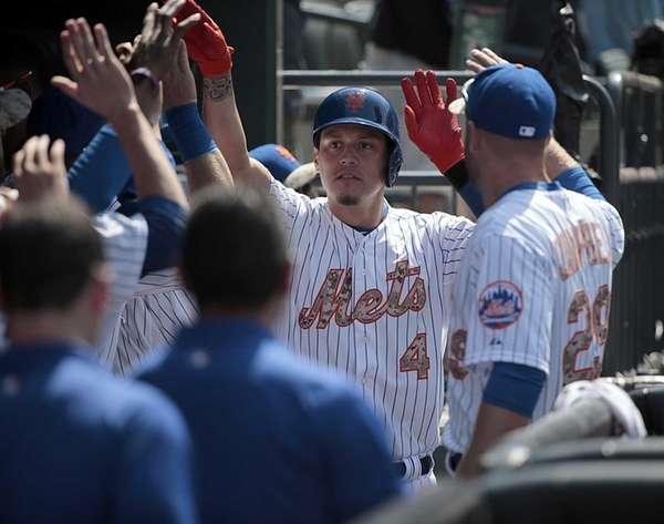 New York Mets shortstop Wilmer Flores is greeted