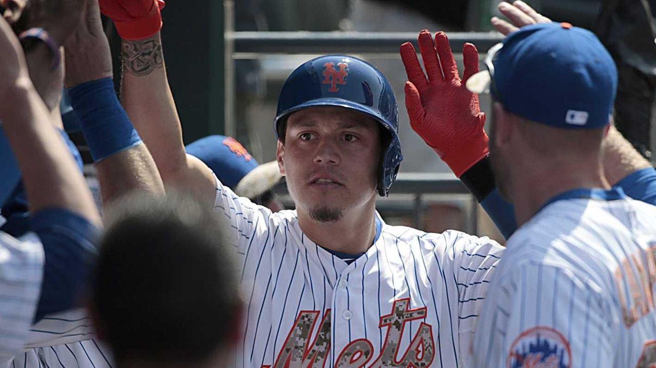 New York Mets shortstop Wilmer Flores is greeted
