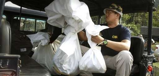 A Malaysian forensic team personnel carries bags of