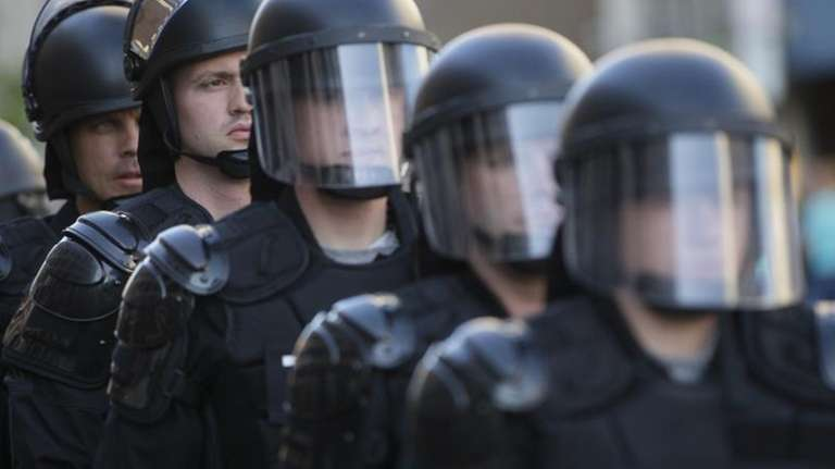 Riot police stand in formation as a protest