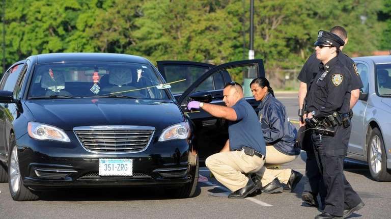 NYPD investigators collect evidence from a car outside