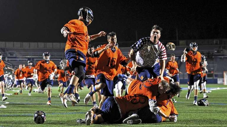 Manhasset rushes its goalie Henry Mulholland after defeating