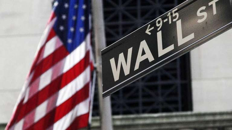 The American flag and Wall Street sign outside