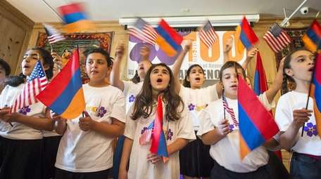 Waving American and Armenian flags, the youth choir