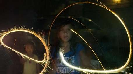 Children twirl sparklers during Fourth of July celebrations