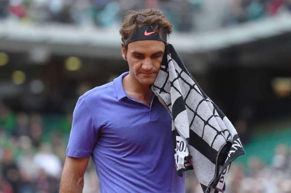 Roger Federer wipes his face with a towel