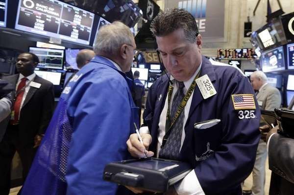 Trader William McInerney, right, works on the floor