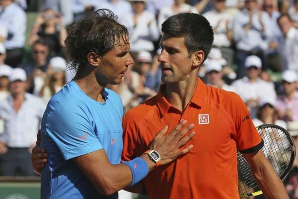 Serbia's Novak Djokovic hugs Spain's Rafael Nadal, left,