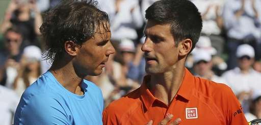 Serbia's Novak Djokovic hugs Spain's Rafael Nadal, left,