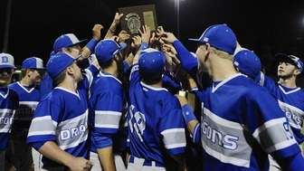 Division players hoist their championship plaque after the