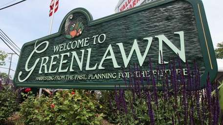 A Welcome to Greenlawn sign shows the way