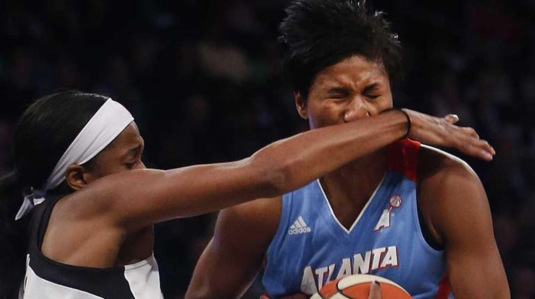 The Atlanta Dream's Angel McCoughtry, center, gets hit