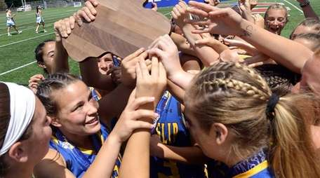 West Islip players hoist the championship plaque after
