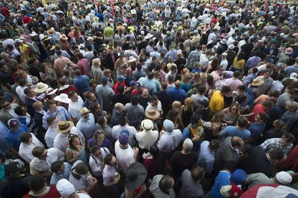 Horse racing fans stand at Belmont Park for