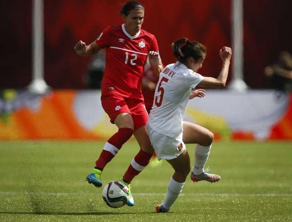 Canada's Christine Sinclair, left, tries to get past