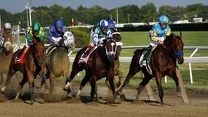 American Pharoah (5), far right, leads the field