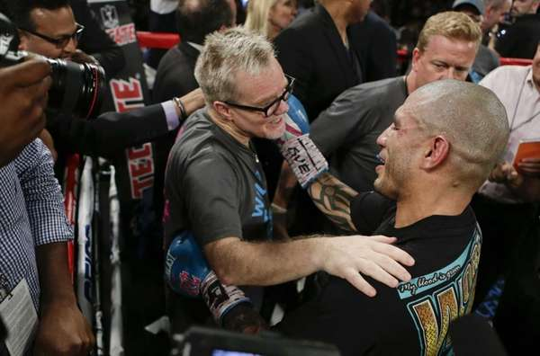 Freddie Roach, left, celebrates with Miguel Cotto, right,