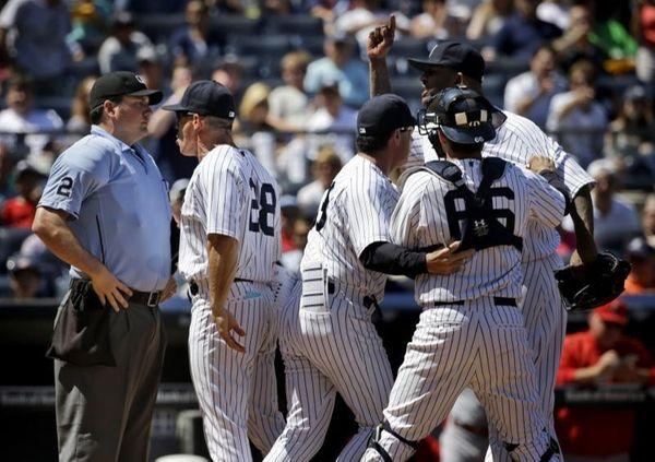 Teammates hold back New York Yankees starting pitcher