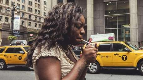 A woman smokes in New York City in