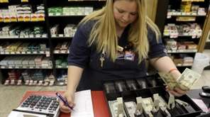 Amy Jennewein reconciles a cash register drawer on