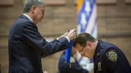 Police officer Joseph Arbia, right, is awarded the
