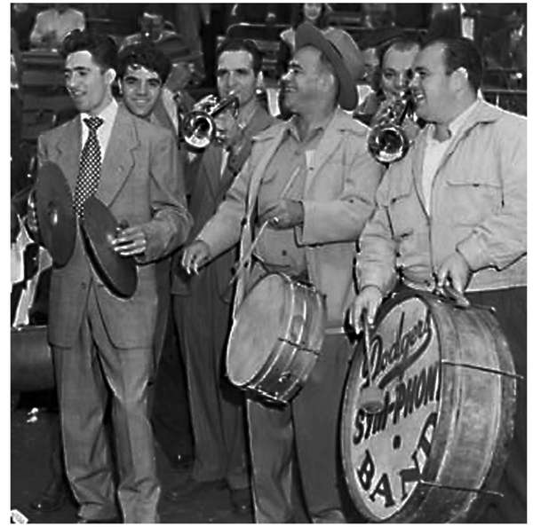 Armand Soriano, left, playing the cymbals, stands next