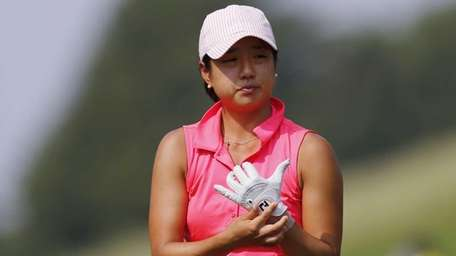 Kelly Shon adjusts her glove before teeing off
