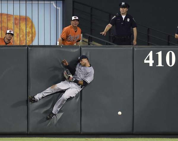 The Yankees' Mason Williams hits the wall after