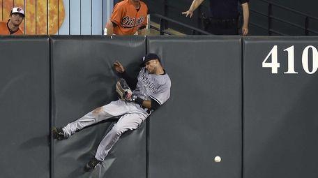 The Yankees' Mason Williams hits the wall after