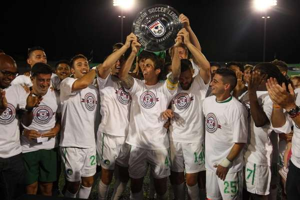 The Cosmos hoist the spring championship plate after