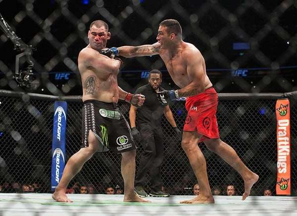 Fabricio Werdum, right, lands a punch on Cain