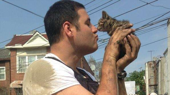NYPD Officer John Passarella nuzzles the kitten he