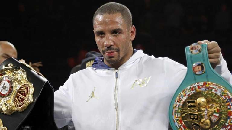 Andre Ward holds up his championship belts after