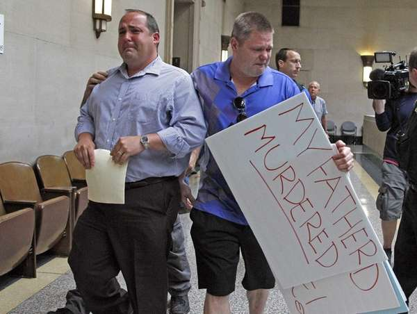 Edward Ross, left, son of Edward Ross, reacts