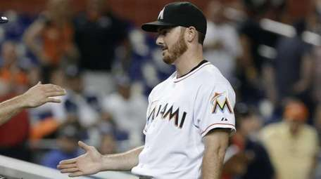 Miami Marlins relief pitcher Sam Dyson, right, and