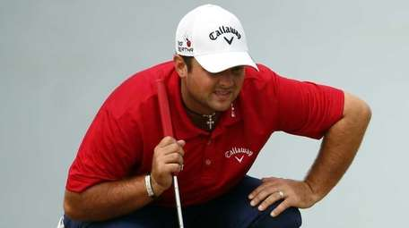Patrick Reed lines up a putt on the