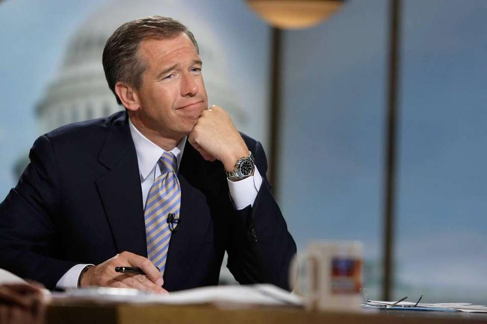 Moderator Brian Williams watches a video which pays