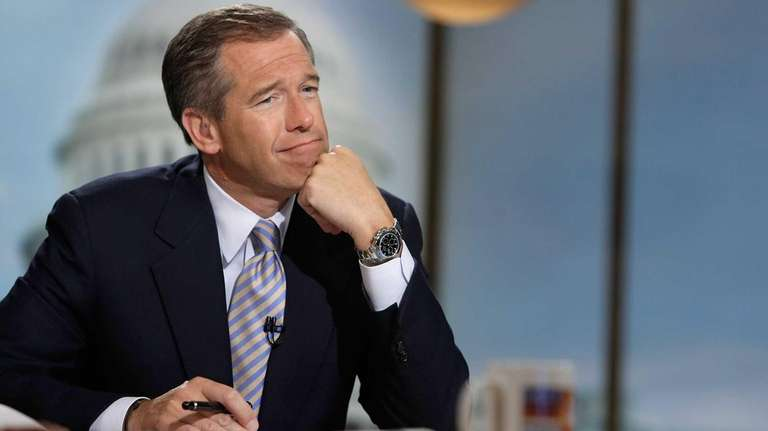Moderator Brian Williams watches a video paying tribute