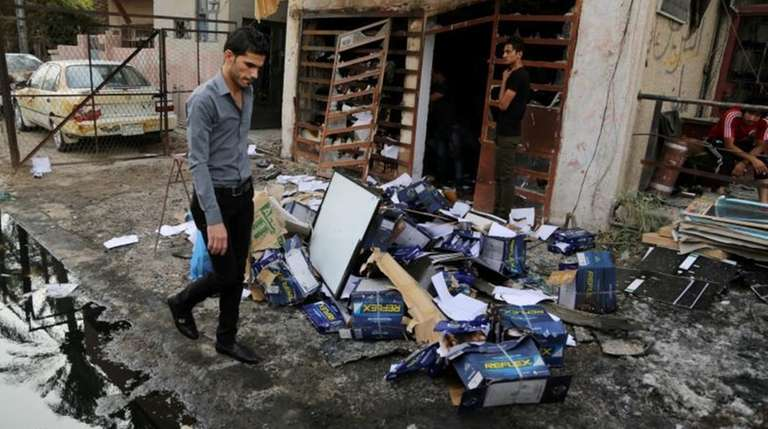 Civilians inspect the site of a car bomb